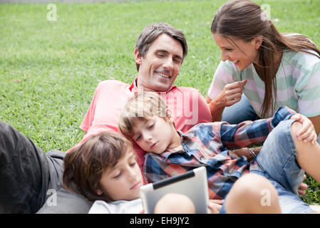 Family with two children spending afternoon at park, young boys using digital tablet - Stock Photo