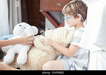 Little boy playing with teddy bear - Stockfoto