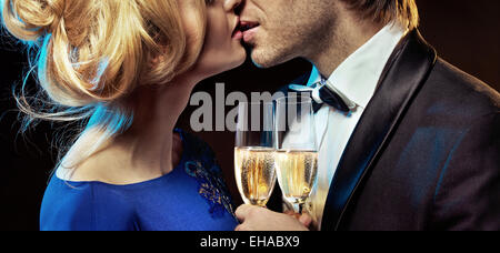 Elegant couple kissing and drinking champagne - Stock Photo