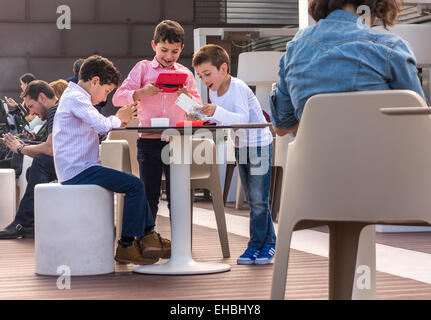 Children playing handheld computer games while grown ups, parents, are all looking at their smartphones on a Sunday - Stock Photo