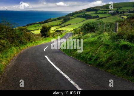 Road near Torr Head with green fields in background. Antrim Coast Northern Ireland - Stock Photo