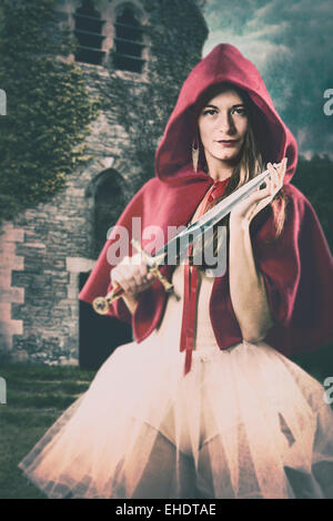 Woman wearing a red cape holding a small sword - Stock Photo
