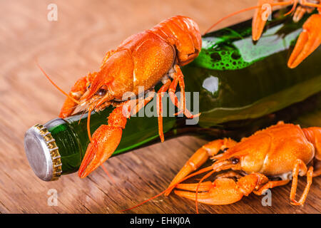 beer in a glass bottle and crayfish close-up on wooden background - Stock Photo