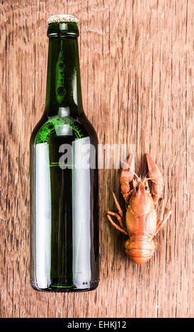 beer in a glass bottle and cancer on the wooden background - Stock Photo