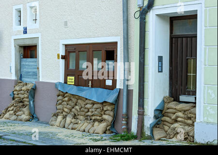 Flood control measures, sandbags and a protective wall of steel slats in front of front doors and a garage door, - Stock Photo