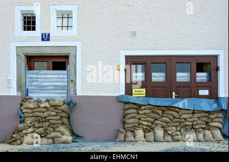 Flood control measures, sandbags and a protective wall of steel slats in front of a front door and a garage door - Stockfoto