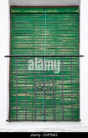 Green venetian blind keeps the sunlight penetrating the window of an Andalucian house. - Stock Photo