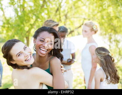 Bridesmaid and friend dancing during wedding reception in domestic garden - Stock Photo