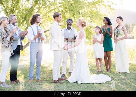 Young couple and guests during wedding ceremony in domestic garden - Stock Photo