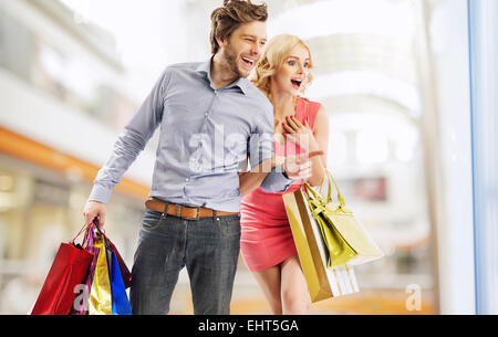 Young laughing couple staring at the shop window - Stock Photo