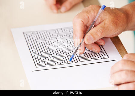 Hand of senior man with pen doing memory training with a paper maze - Stock Photo