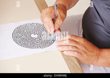 Old man doing memory training with paper maze in a nursing home - Stock Photo