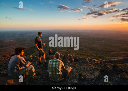 Hikers enjoy the sunset at the summit of active Volcano Telica, a popular tour from the NW city of Leon; Leon, Nicaragua - Stock Photo