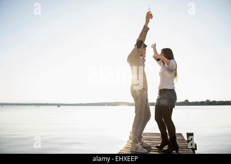 Lake sunset jetty young couple dancing - Stock Photo