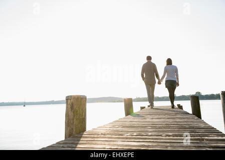 Couple walking on wooden jetty sunset - Stock Photo