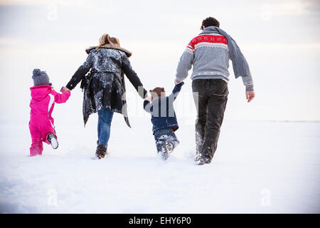 Family walking in snow - Stock Photo