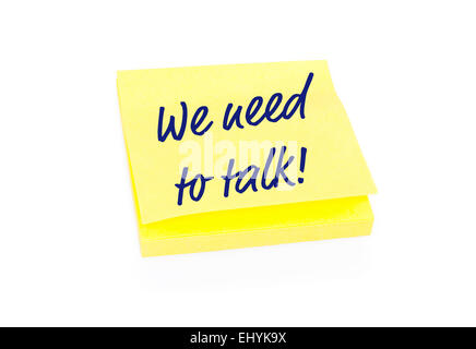 Yellow sticky note on block with text We Need To Talk - Stock Photo