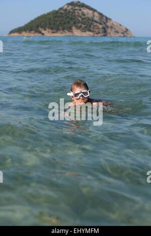 Boy wearing goggles swimming in the sea - Stock Photo