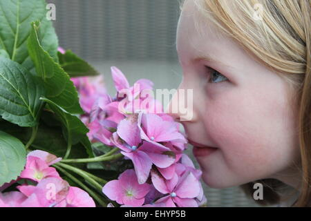 Girl smelling flowers - Stock Photo