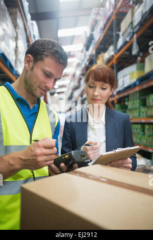 Worker and manager scanning package in warehouse - Stock Photo