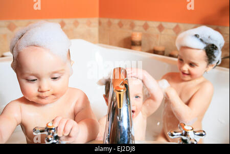 Funny little girl and her cute baby brother having fun taking bath together playing in water with foam with colorful - Stock Photo