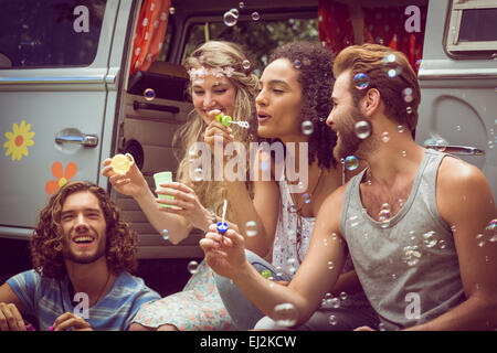 Hipsters blowing bubbles in camper van - Stock Photo