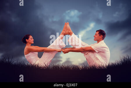 Composite image of peaceful couple sitting in boat position together - Stock Photo