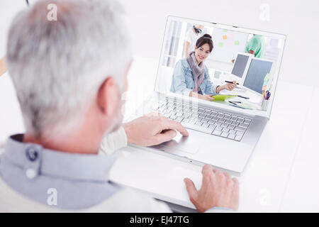 Composite image of closeup rear view of a grey haired man using laptop at desk - Stock Photo