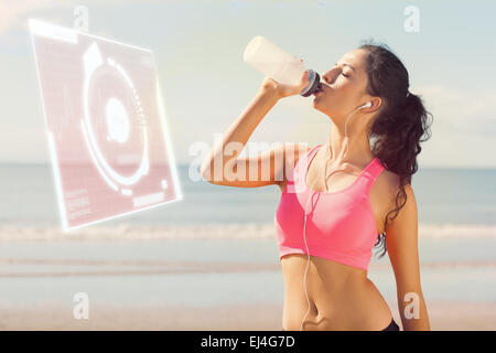 Composite image of beautiful healthy woman drinking water on beach - Stock Photo