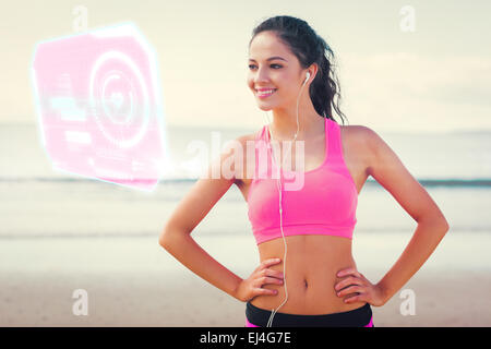 Composite image of beautiful smiling healthy with earphones on beach - Stock Photo