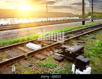 Green grass near rails along industrial station - Stock Photo