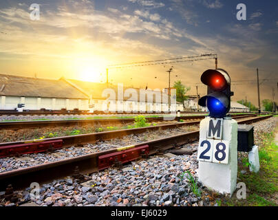 Railway semaphore near industrial station at sunset - Stock Photo