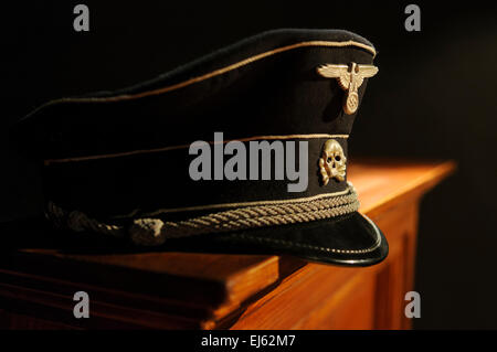 Waffen SS Officer's hat sitting on a mantelpiece - Stock Photo