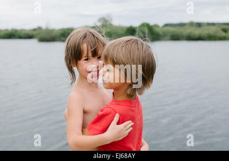 Cute laughing fraternal twins enjoying their time at the beach on hot summer day. Brother and sister hugging. Having - Stock Photo