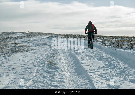 Mountain biker heading towards Win Hill in winter, Peak District, Derbyshire, England, UK. - Stock Photo