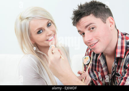 couple sitting together at home, and eating sushi - Stock Photo
