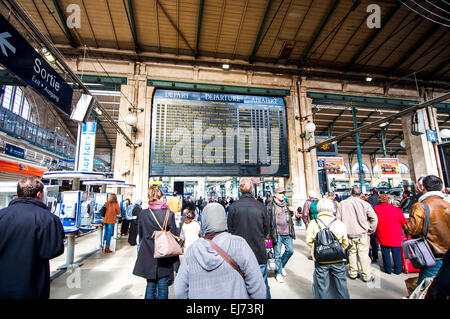 Travellers standing in front of the large departure times board at the Gare Du Nord train station in Paris, France. - Stock Photo