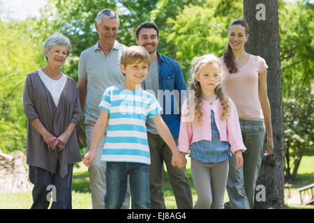 Happy extended family standing at park - Stock Photo