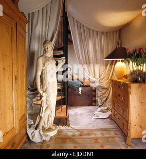 Classical marble statue in eighties hall with heavy cream drapes on ceiling and beside spiral staircase - Stockfoto