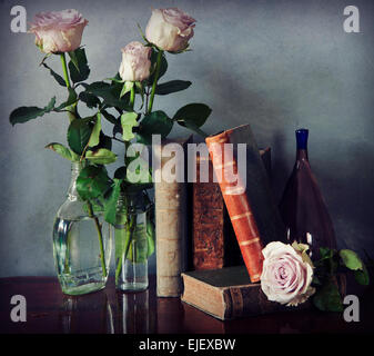 Interior still life: composition of antique books on a wooden table, pink roses in a glass bottle and a purple Murano - Stockfoto