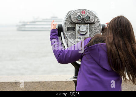 Woman using binoculars at Upper New York Bay, Ellis Island, Jersey City, New York State, USA - Stock Photo
