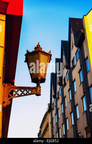 Old street lamp on the wall of the house on the street with the other buildings in Riga. Latvia - Stock Photo
