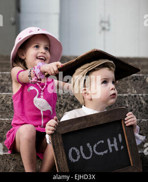 Naughty sister hits her brother over the head with chalkboard - Stock Photo