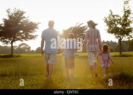 A family, two parents and two children walking hand in hand across grass outdoors in the summer. - Stock Photo