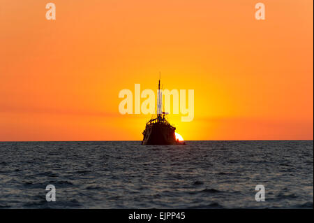An old wooden ship sits at sea and watches the fantasy sun set in the background. - Stock Photo