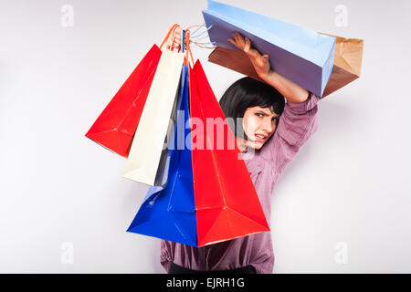young brunette woman covered in shopping bags - Stock Photo
