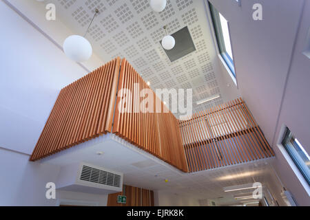 Timber balcony above main communal area of modern college building - Stock Photo