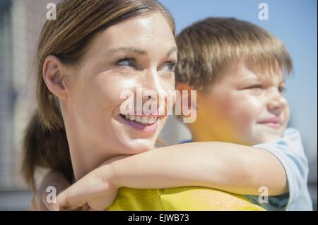 Mother giving her son (6-7) piggyback ride - Stock Photo