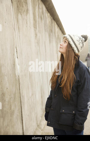 Teenage Girl in front of Berlin Wall, Berlin, Germany - Stock Photo
