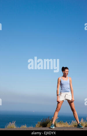 Sport Woman Standing against Ocean and Blue Sky - Stock Photo